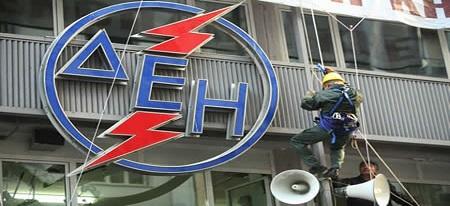 Gréviste descendant en rappel le long du logo DEI sur un immeuble.