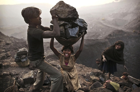 A young woman stumbles as she tries to carry a large basket of coal as they illegally scavenge at an open-cast mine in the village of Bokapahari in the eastern Indian state of Jharkhand.